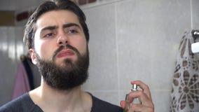 Przystojny mężczyzna używa pachnidło przed lustrem Przystojny mężczyzna stosuje pachnidło przy rankiem fotografia royalty free