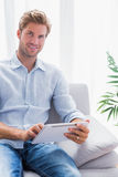 Przystojny mężczyzna używa pastylka komputer osobistego na jego leżance Obraz Royalty Free