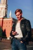 Przystojny mężczyzna używa telefon podczas gdy stojący przeciw tłu Kremlin zdjęcia royalty free