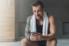 Przystojny mężczyzna use telefon komórkowy w gym zdjęcie stock
