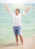 Przystojny mężczyzna w koszulowych cieszy się morza i podnosić rękach w niebie Obraz Royalty Free