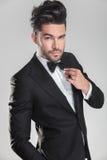 Przystojny mężczyzna w smokingu ajusting jego łęku krawat obrazy royalty free