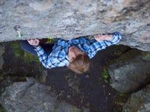 Przystojny mężczyzna w szkockiej kraty koszula wspina się na skale Obraz Stock