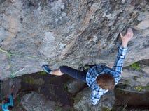 Przystojny mężczyzna w szkockiej kraty koszula wspina się na skale Zdjęcie Royalty Free
