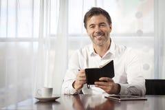 Przystojny mężczyzna Writing Przy sklep z kawą zdjęcia royalty free