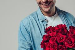 Przystojny mężczyzna z czerwonymi różami zdjęcia stock