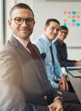 Przystojny mężczyzna z dwa pracownikami przy stołem zdjęcie stock