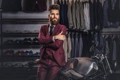 Przystojny mężczyzna z eleganckim włosy i brodą ubierał w rocznika czerwonym kostiumu pozuje blisko retro sporta motocyklu przy m fotografia stock