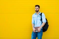 Przystojny mężczyzna z plecakiem na kolorze żółtym obraz royalty free