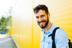 Przystojny mężczyzna z plecakiem na kolorze żółtym obrazy royalty free