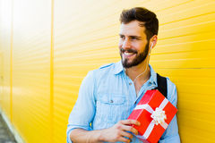 Przystojny mężczyzna z plecakiem na kolorze żółtym fotografia stock