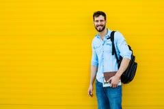 Przystojny mężczyzna z plecakiem na kolorze żółtym zdjęcia royalty free