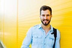 Przystojny mężczyzna z plecakiem na kolorze żółtym obrazy stock