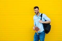 Przystojny mężczyzna z plecakiem na kolorze żółtym zdjęcia stock