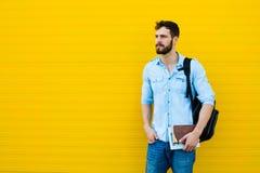 Przystojny mężczyzna z plecakiem na kolorze żółtym zdjęcie stock