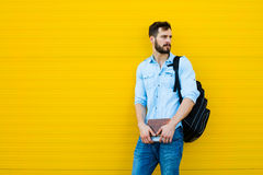 Przystojny mężczyzna z plecakiem na kolorze żółtym fotografia royalty free