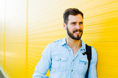 Przystojny mężczyzna z plecakiem na kolorze żółtym zdjęcie royalty free