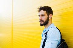 Przystojny mężczyzna z plecakiem na kolorze żółtym obraz stock