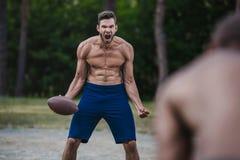 Przystojny męski gracz futbolu wrzeszczy i trzyma balowy na sądzie Zdjęcie Stock