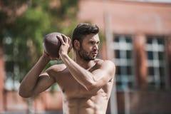 Przystojny męski gracz futbolu z piłką na sądzie Zdjęcie Royalty Free