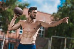 Przystojny męski gracz futbolu z piłką na sądzie Fotografia Stock