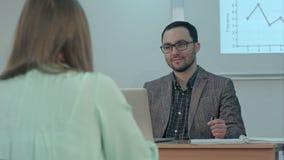 Przystojny męski nauczyciel ono uśmiecha się i opowiada z uczniami przy lekcją zdjęcie wideo