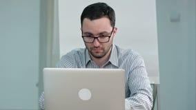 Przystojny męski nauczyciel pisać na maszynie na laptopie w szkłach zbiory wideo
