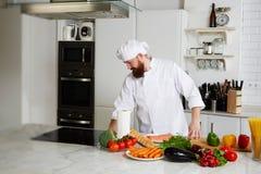 Przystojny męski szef kuchni w mundurze przygotowywa jego kuchnię dla zaczynał gotować Fotografia Stock