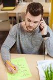 Przystojny męski uczeń komunikuje na telefonie Obrazy Royalty Free