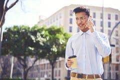 Przystojny męski uczeń opowiada z przyjaciółmi na telefonie komórkowym z eyeglasses obraz royalty free