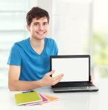 Przystojny Męski uczeń pokazuje pustego ekran laptop obrazy stock
