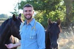Przystojny męski weterynarz ono uśmiecha się blisko do koni Obraz Royalty Free