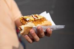 Przystojny młodego człowieka łasowania hot dog obrazy stock