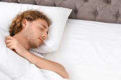 Przystojny młodego człowieka dosypianie na poduszce bedtime obrazy stock