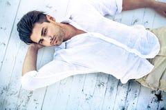 Przystojny młodego człowieka lying on the beach na białej drewnianej powierzchni fotografia stock