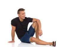 Przystojny młodego człowieka obsiadanie Relaksujący Na podłoga fotografia stock
