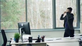Przystojny młodego człowieka urzędnik tanczy w biurze i zdejmuje kurtkę cieszy się wolność i dobrego nastrój korporacyjny zbiory wideo
