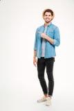 Przystojny młodego człowieka wskazywać oddalony i uśmiechnięty podczas gdy stojący Fotografia Stock