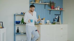 Przystojny młody śmieszny mężczyzna taniec, śpiew w kuchni i podczas gdy surfujący ogólnospołecznych środki na jego smartphone w  zbiory wideo