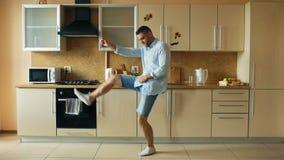 Przystojny młody śmieszny mężczyzna taniec w kuchni w ranku w domu i zabawę na wakacjach zdjęcie royalty free