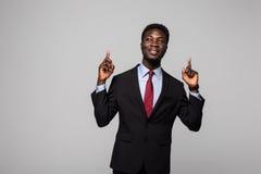 Przystojny młody Afrykański mężczyzna w kostiumu wskazywać up i uśmiechnięty podczas gdy stojący przeciw popielatemu tłu obraz stock