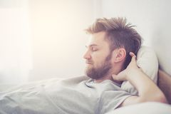 Przystojny młody amerykański męski dosypianie w łóżko opieki zdrowotnej pojęciu w domu - Obraz Stock