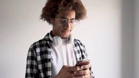 Przystojny młody amerykanin afrykańskiego pochodzenia mężczyzna używa jego telefon komórkowego w domu pojedynczy bia?e t?o zdjęcie wideo