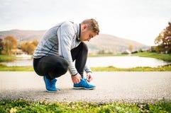 Przystojny młody biegacz wiąże shoelaces Fotografia Royalty Free