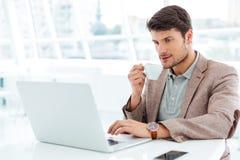Przystojny młody biznesmen ma filiżankę kawy i używa laptop fotografia stock