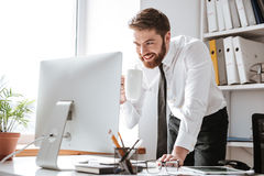Przystojny młody biznesmen patrzeje komputer fotografia stock