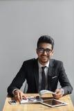 Przystojny młody biznesmen uśmiechnięty i patrzeje kamerę w kawiarni podczas gdy siedzący przeciw popielatemu tłu Fotografia Royalty Free