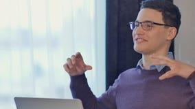 Przystojny młody biznesmena obsiadanie przy jego biurkiem, odświętność sukces z rękami podnosić, gestykulujący dużo zdjęcia royalty free