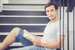 Przystojny młody biznesowy azjatykci mężczyzna w przypadkowych ubrań czytelniczej książce z czasem wolnym w żywym pokoju Zdjęcia Stock