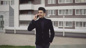 Przystojny młody biznesowy mężczyzna opowiada na smartphone uśmiecha się szczęśliwą jest ubranym kostium kurtkę outdoors Zdjęcia Royalty Free